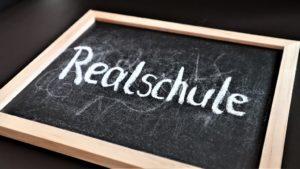 Tafel mit Text Realschule schräg